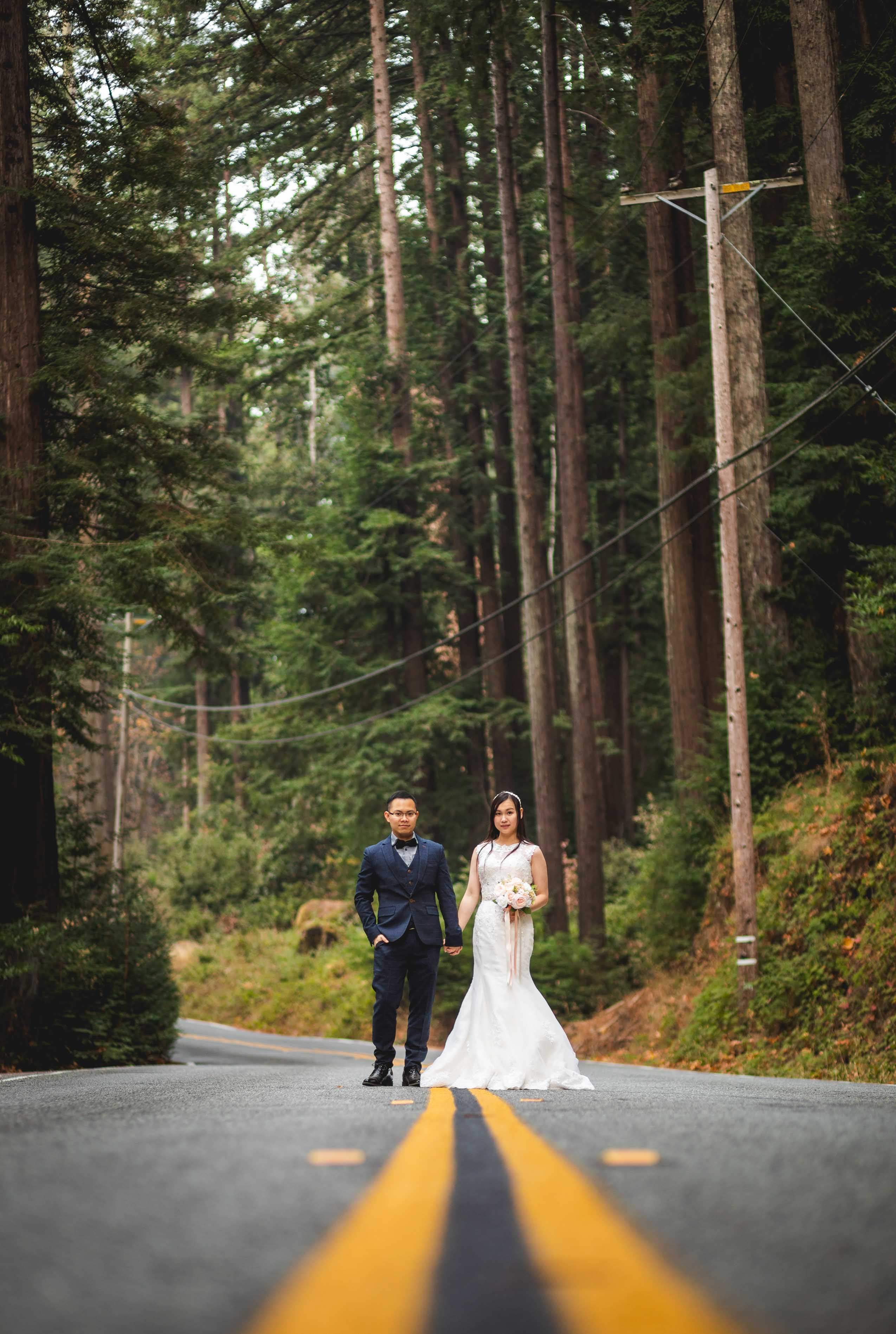 bride and groom standing in a long road holding hands