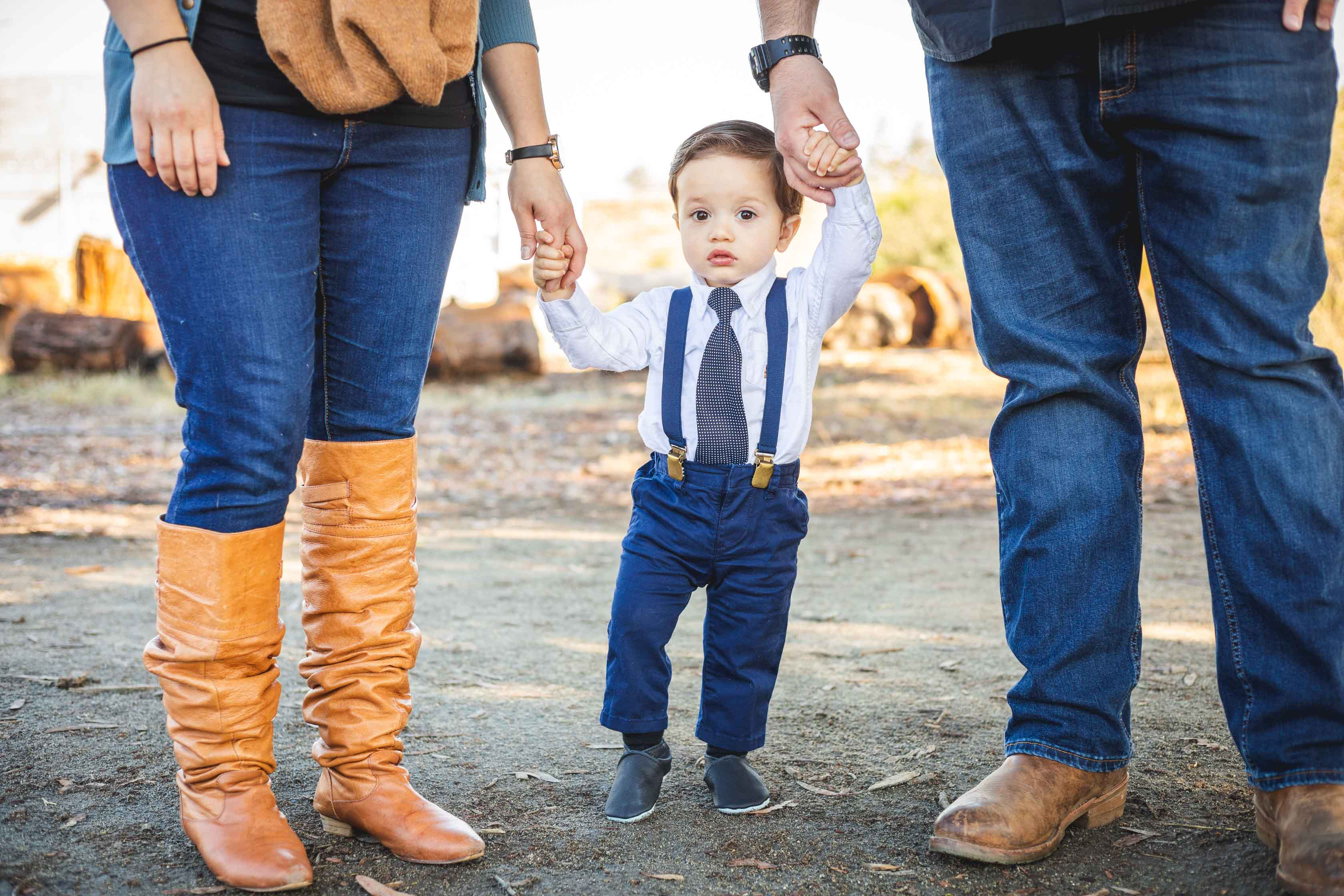 little boy with parents holding his hands