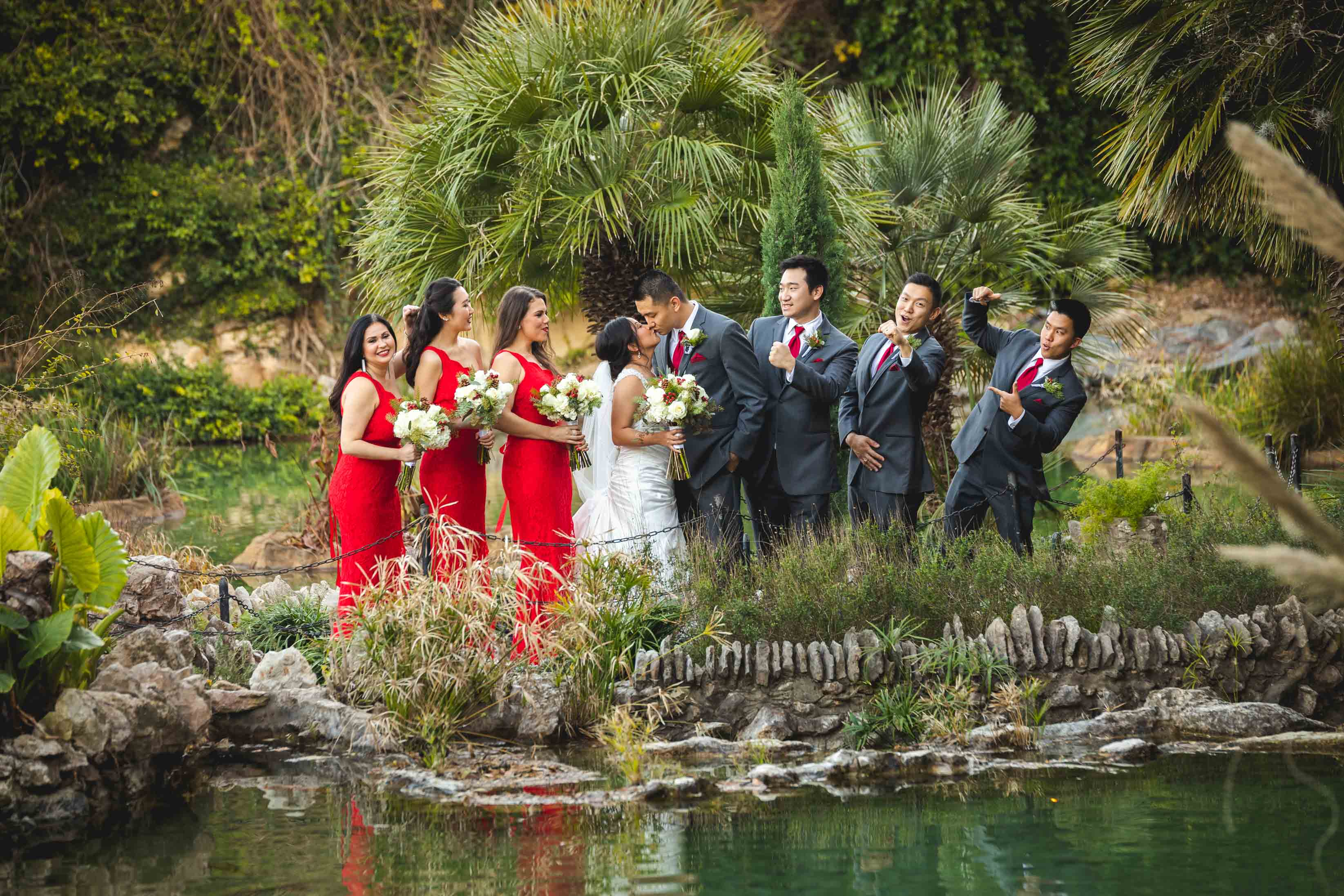 bridal party excited for groom and bride kissing in japanese garden