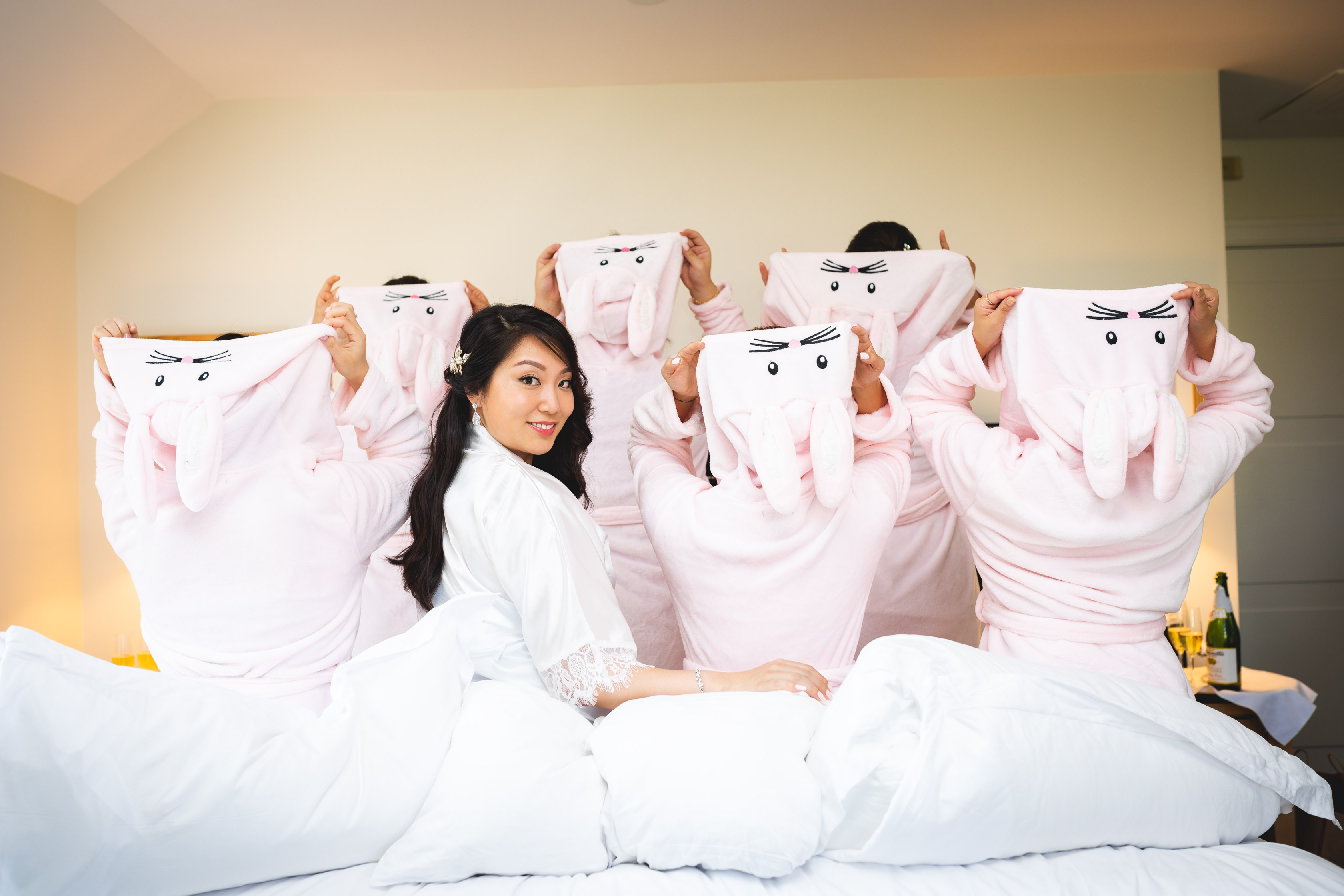 bride and bridesmaids on the bed wearing bunny sweaters