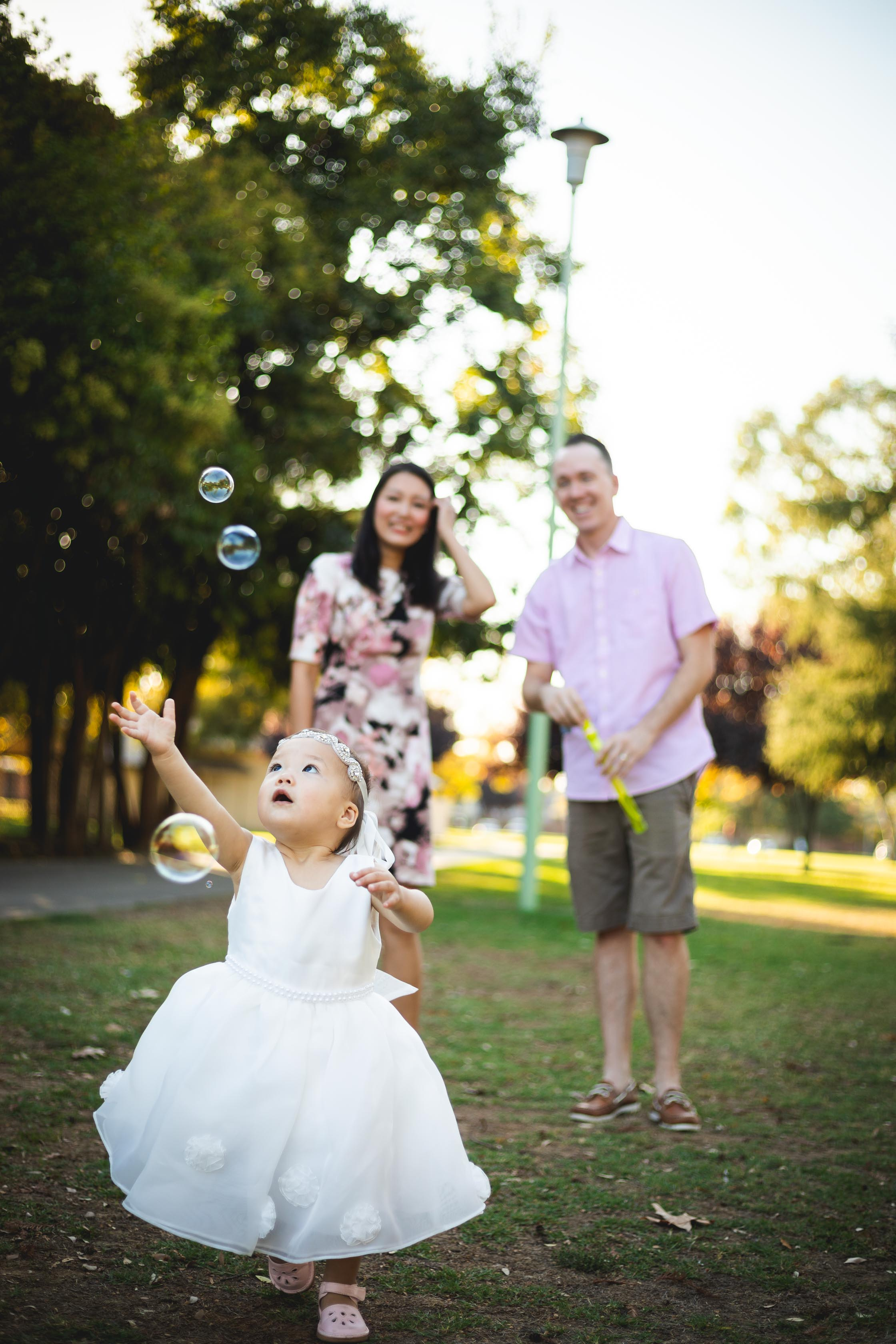family photoshoot with baby chasing bubbles