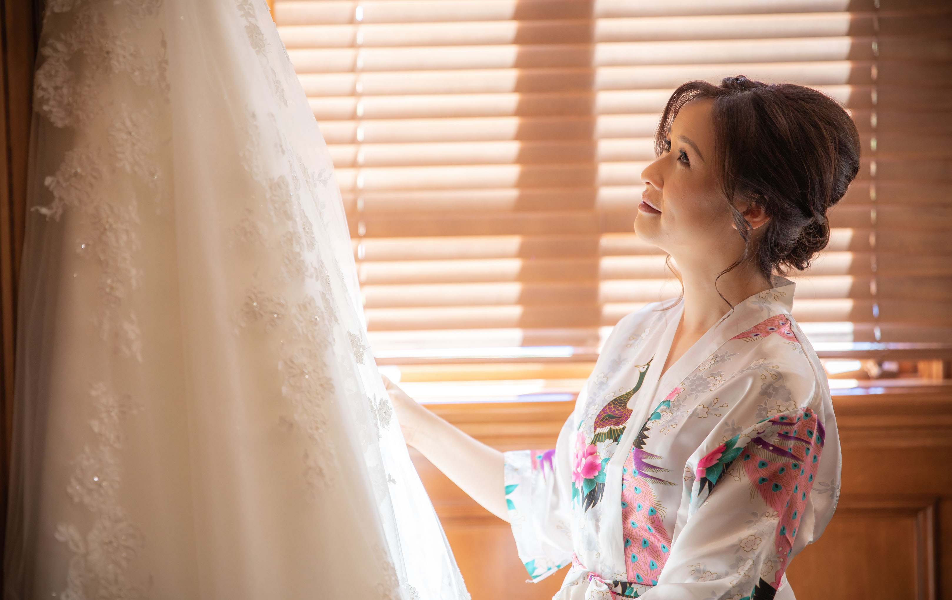 bride looking at wedding dress longingly