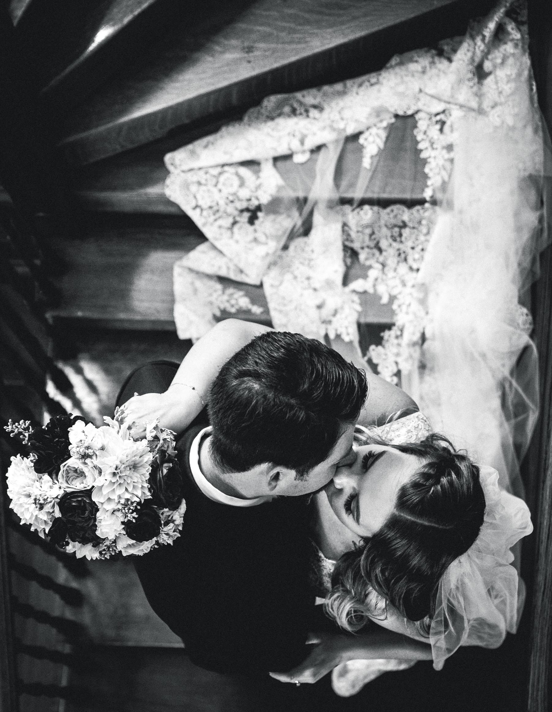 bride and groom kissing on stairs from above