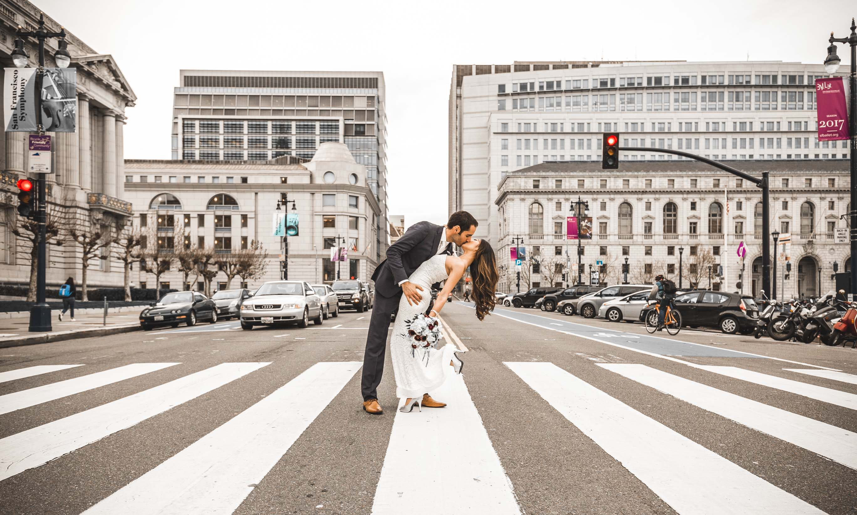couple passionately kissing in front of city hall on the road crosswalk