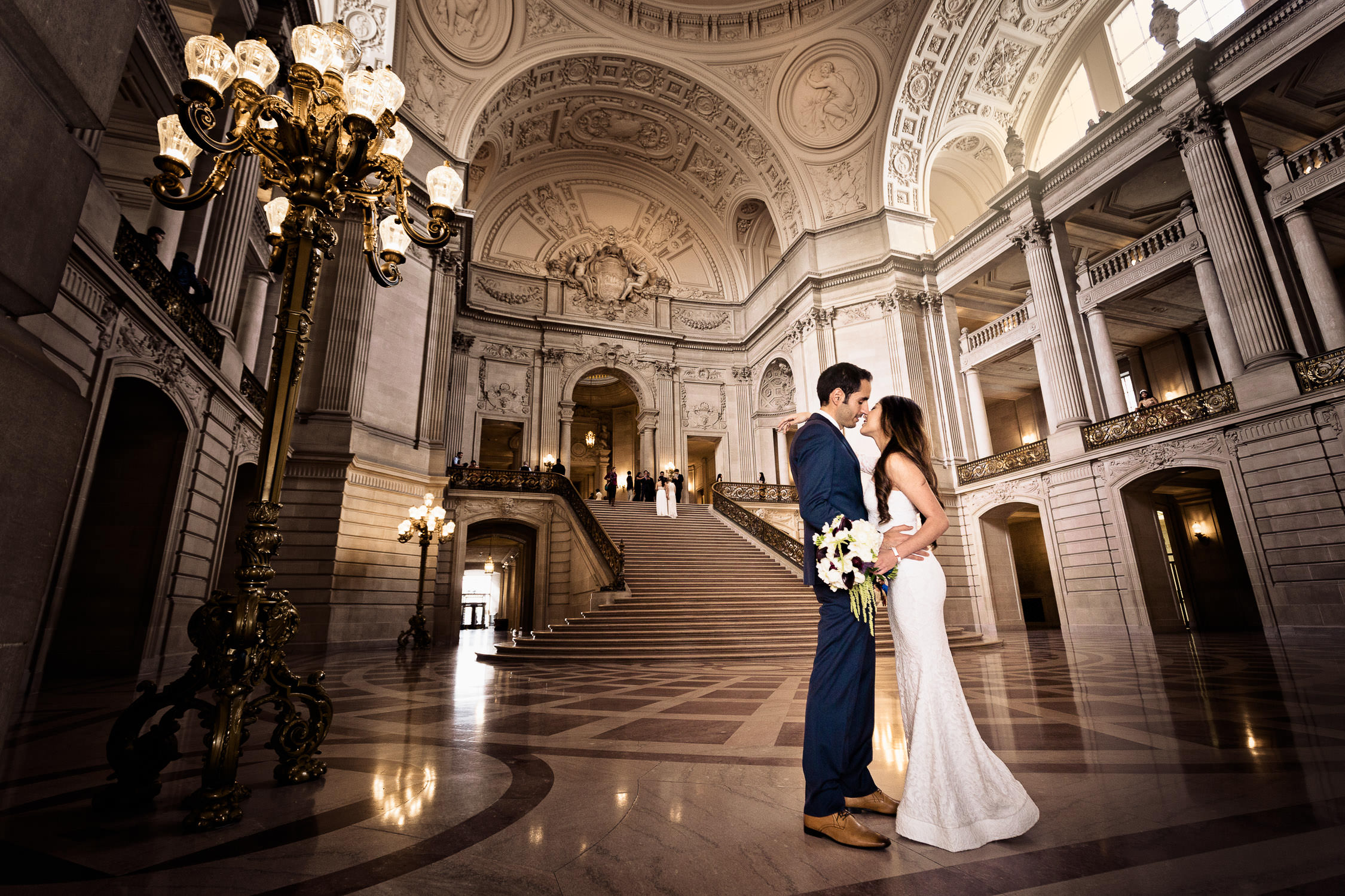 couple on the floor of san francisco city hall with lights