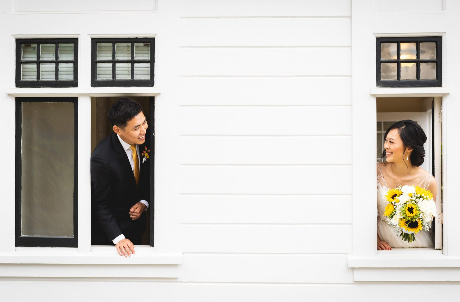 bride and groom peaking out window